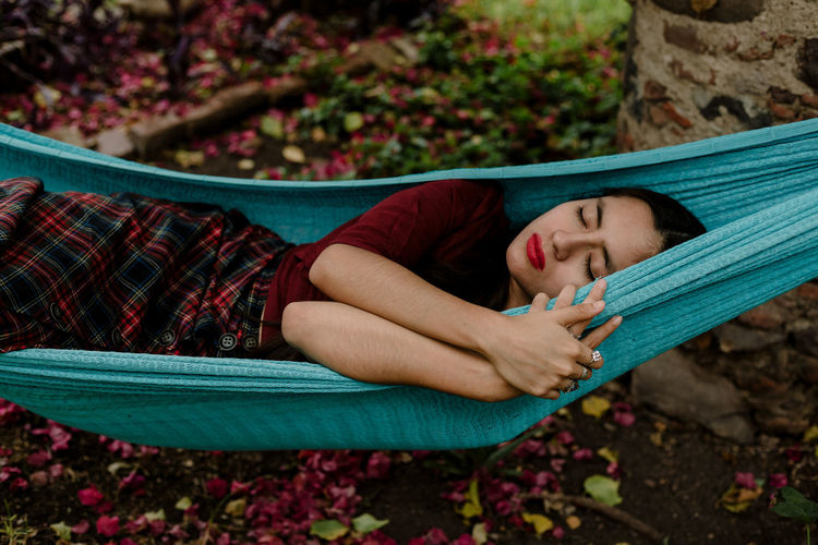 Young woman sleeping on hammock