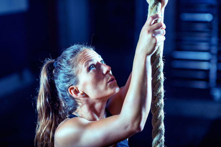Close-up of female athlete climbing on rope in gym