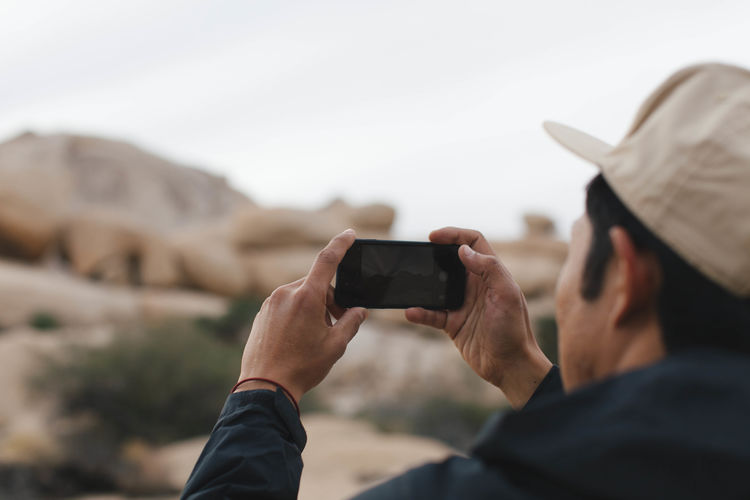 Close-up of man photographing with smart phone