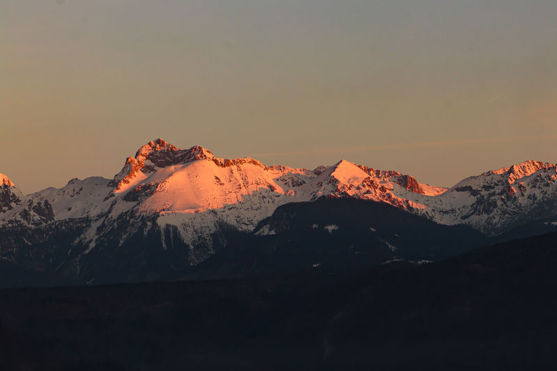 Scenic view of snowcapped mountains against sky during sunset