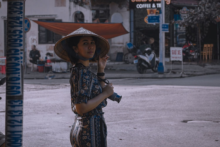 Full length portrait of woman standing in city