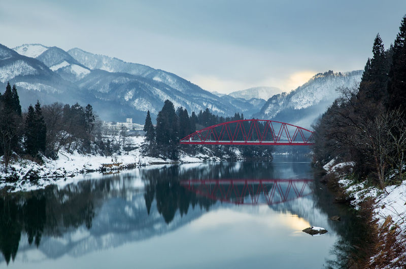 Arch bridge over lake against snowcapped mountains