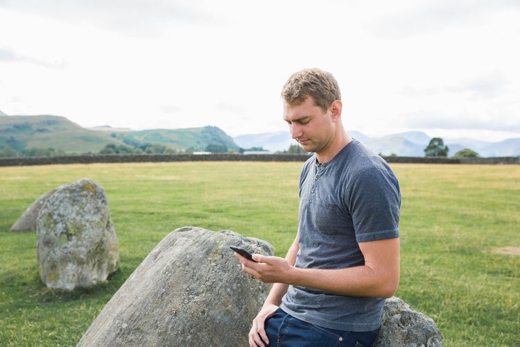 One Person Young Adult Technology Rock Land Rock - Object Wireless Technology Lifestyles Young Men Nature Countryside Communication Cell Phone  Mobile Device United Kingdom International Travel England, UK Lake District Travel Rural Landscape