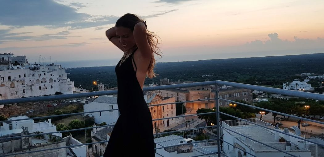 Side View Of Woman Standing On Building Terrace During Sunset