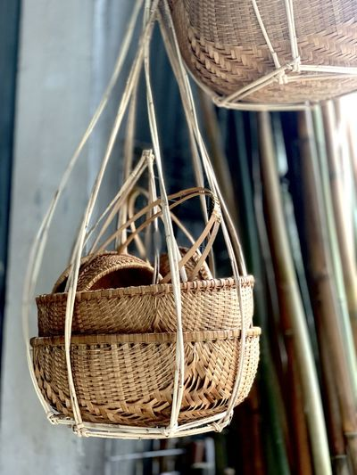 Close-up of wicker baskets hanging indoors