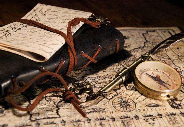 Close-up of book and navigational compass