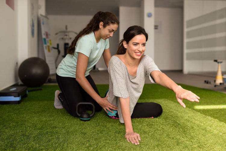 Physical Therapist Assisting Young Woman
