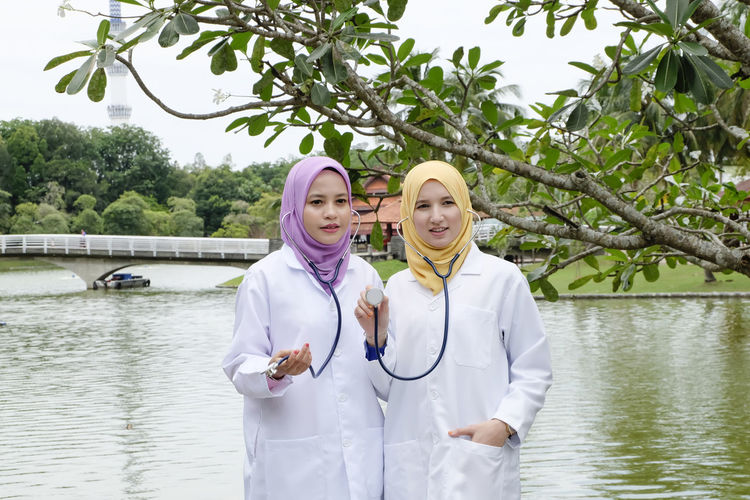 Portrait Of Smiling Female Doctors Holding Stethoscopes While Standing By Lake