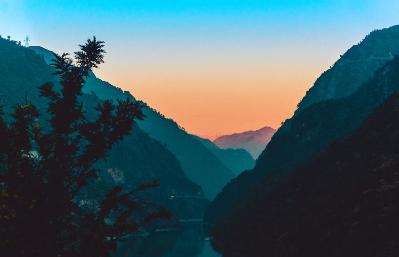 Scenic view of layered mountains against sky at sunset