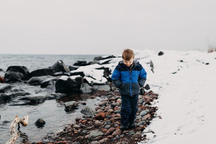 Boy walking at lakeshore on during winter