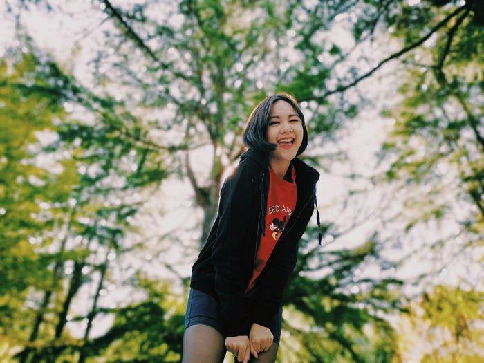 Young woman smiling while standing against trees