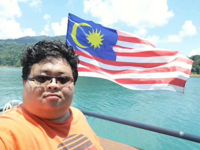 Kenyir Lake Kenyir Lake Resort Malaysia Truly Asia Malaysia Lake View Lake Lakeside Water Waterfall Water_collection Outdoors Outdoor Photography Forest Forest Photography Forestwalk Flag Patriotism Pride Portrait Real People One Person Emotion Day Leisure Activity Nature Front View Sky Males  Looking At Camera Striped Lifestyles Glasses Sunglasses Freedom National Icon Wind
