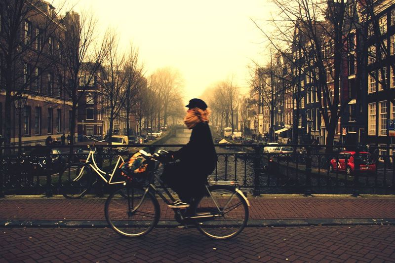 Side view of woman riding bicycle over canal on bridge in city