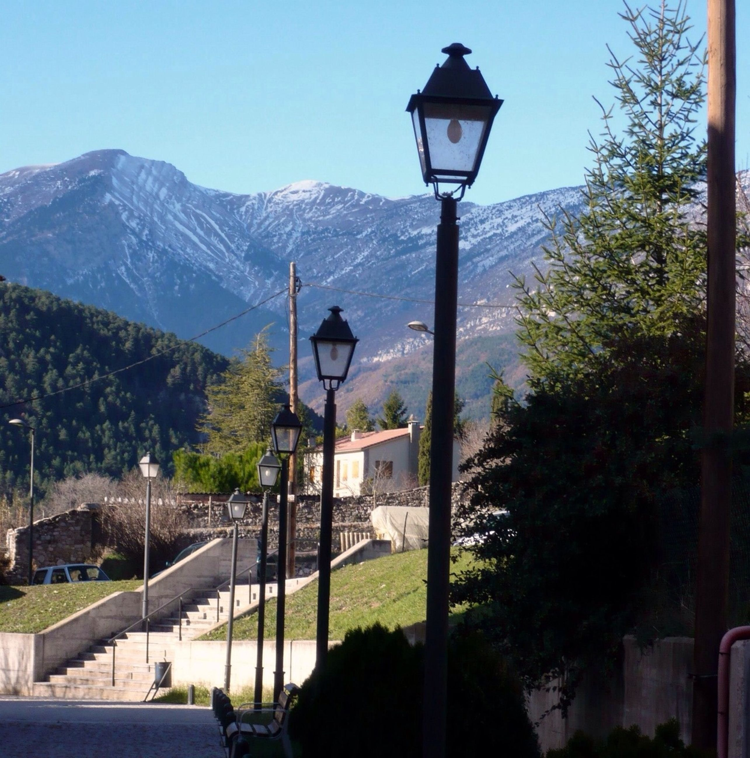 street light, mountain, tree, lighting equipment, clear sky, built structure, lamp post, sky, architecture, building exterior, tranquility, nature, pole, sunlight, cross, mountain range, outdoors, day, beauty in nature, tranquil scene