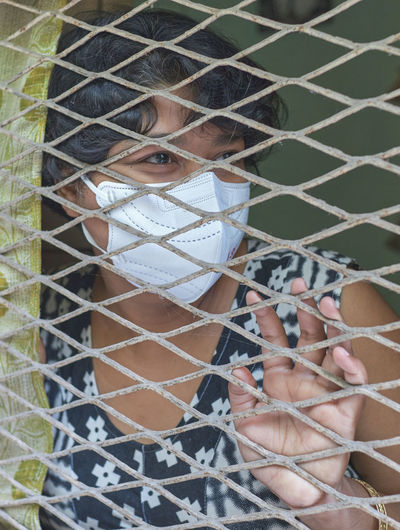 An indian woman looking outside from her house window. at kolkata during covid lockdown period.