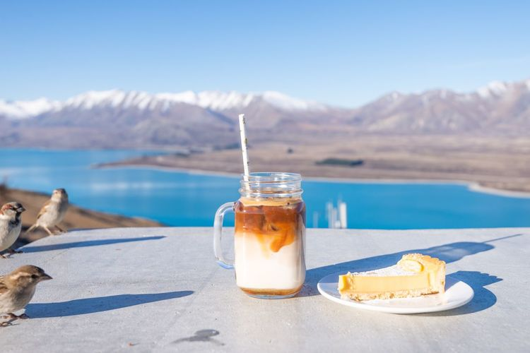 Birds perching by dessert on table with lake in background