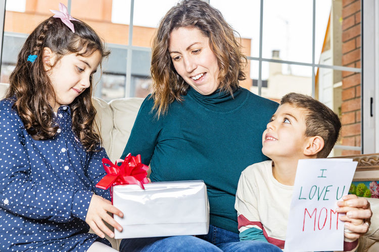 Girl with brother giving gift to mother on sofa in living room at home