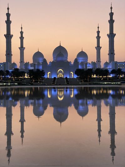 Reflection of mosque in lake against sky