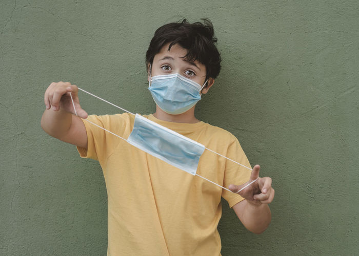 Portrait of boy holding surgical mask against wall