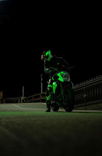 Man riding motorcycle on illuminated christmas lights at night