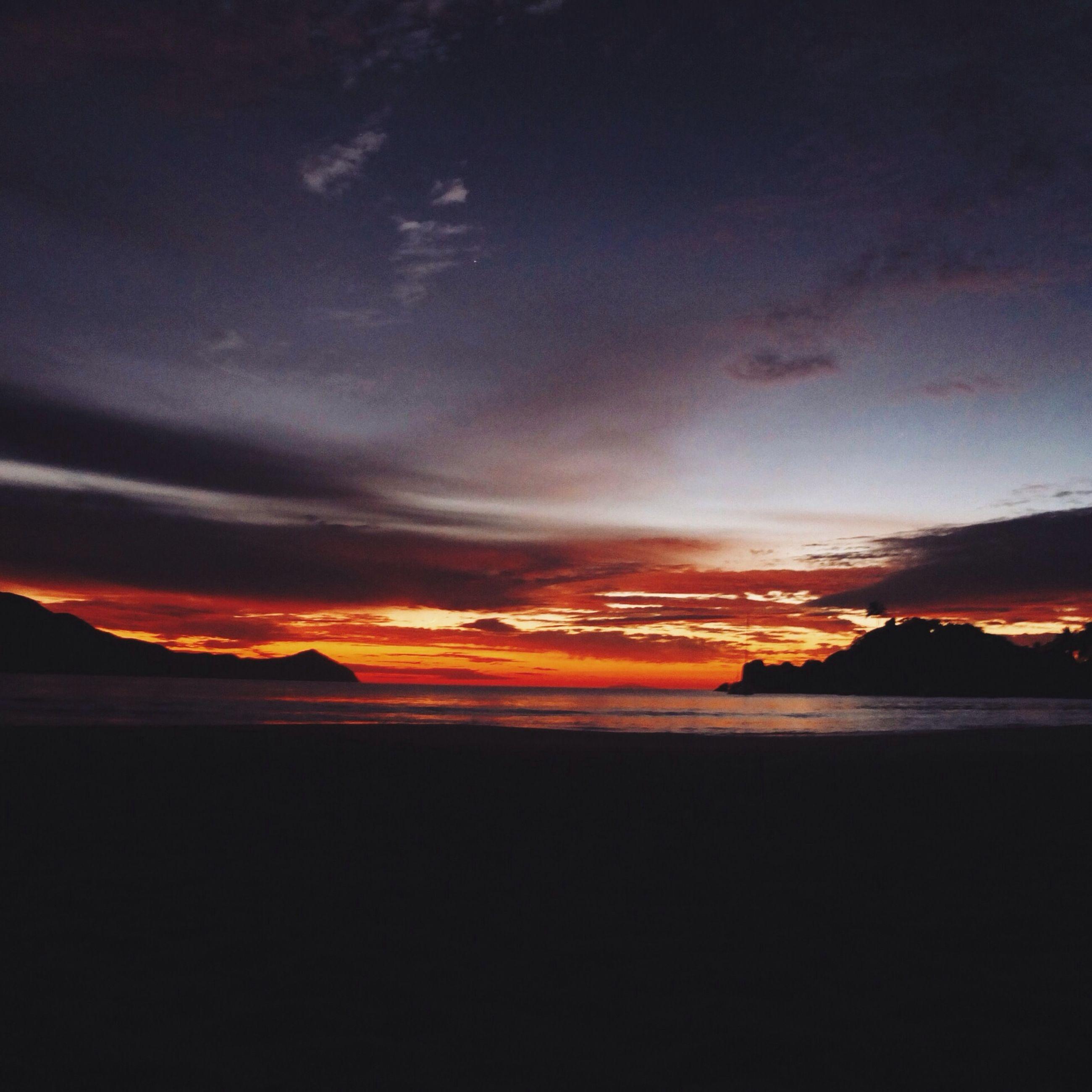 sunset, orange color, scenics, sky, tranquil scene, beauty in nature, tranquility, silhouette, idyllic, nature, sea, cloud - sky, dramatic sky, dark, dusk, water, landscape, cloud, outdoors, majestic
