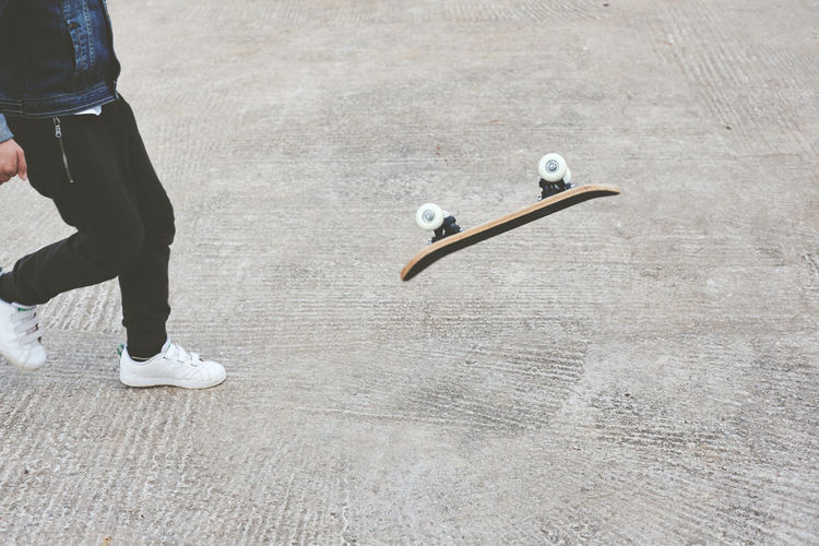 Low section of man with skateboard walking on footpath