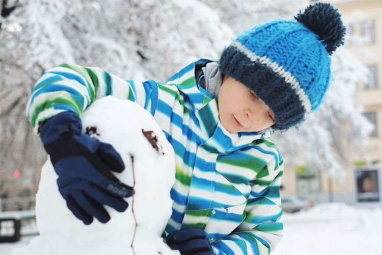 Boy Making Snowman In Yard