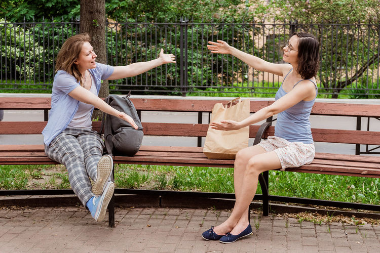 Friends hug each other in the air. greeting girls with social distancing