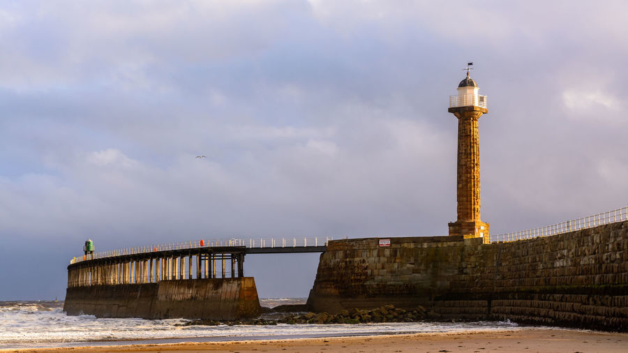Lighthouse By Pier At Beach Against Cloudy Sky