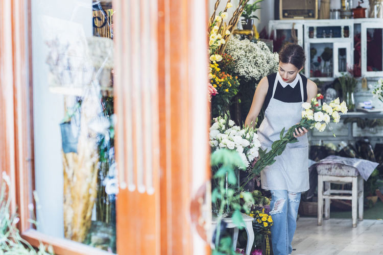Woman standing by potted plants at store
