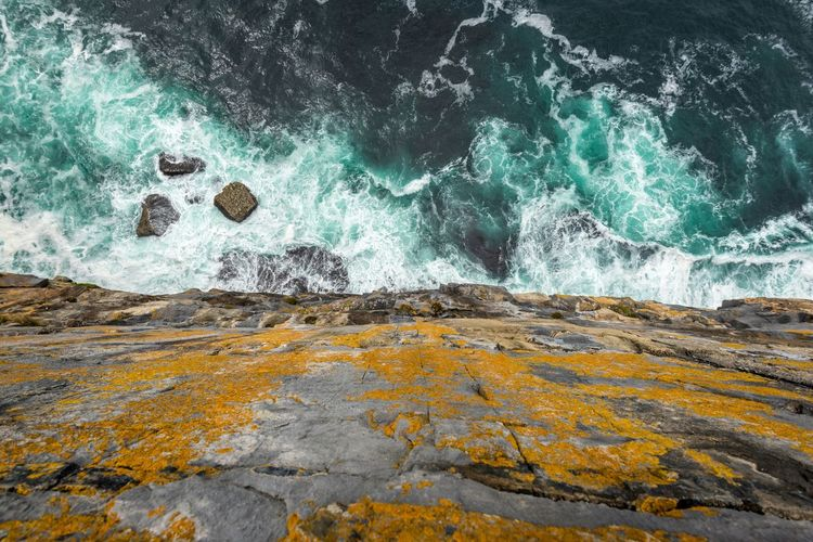 Directly above view of rocky cliff by sea