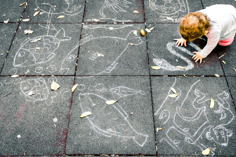 High angle view of child playing on footpath