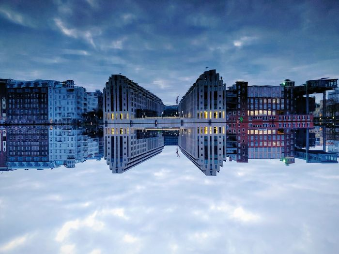 Digital composite image of buildings against cloudy sky