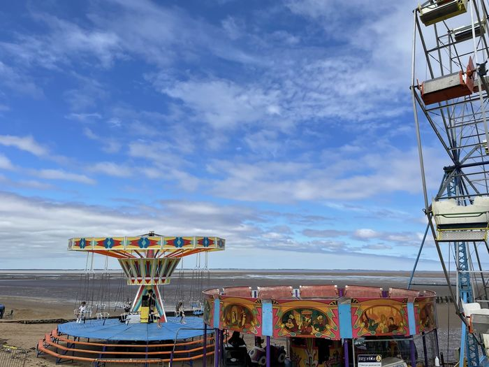 Ferris wheel by sea against sky