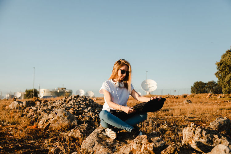 Young woman sitting on field against clear sky