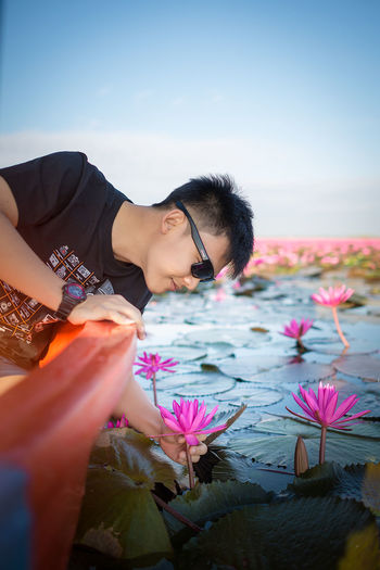 Flowering Plant Flower Young Adult Nature Water Beauty In Nature Lotus Lotus Water Lily Lotus Flower Reach Out Pick Picking Flowers