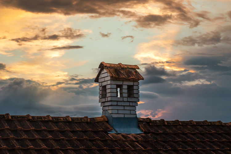 Low angle view of house roof against sky during sunset