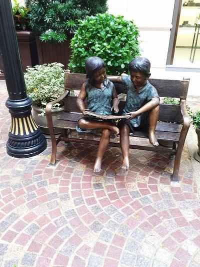 Children enjoying reading a book on a bench Reading On A Bench reading is fun We Love Reading children and reading Children With Book communication by reading Reading And Communication