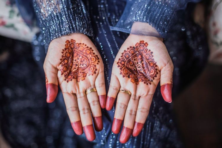 Midsection of woman showing henna tattoo on hands