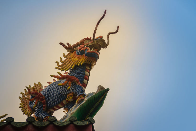 Chinese dragon-headed unicorn statue on the temple roof. Kylin or Kirin on roof in Chinese temple. Chinese Temple Ancient Architecture Chinese Temple Detail Kylin Roof Rooftop Statue Unicorn Unicorn Art Unıcorn Animal Animal Representation Animal Themes Animal Wildlife Animals In The Wild Art And Craft Bird Blue Chinese Dragon Chinese Shrine Chinese Temple Chinese Temple Decoration Chinese Temples Clear Sky Craft Creativity Day Dragon-headed Dragon-headed Unicorn Kirin Kyline Low Angle View Nature No People Representation Roof Tile Rooftop View  Rooftops Sculpture Sky Statue Sunset Temple Roof Temple Roof Tile Unicorns