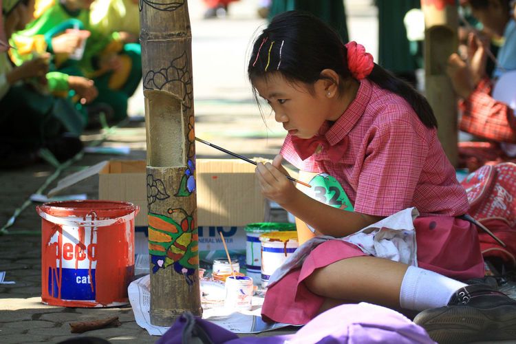 Schoolgirl Painting Bamboo While Sitting Outdoors