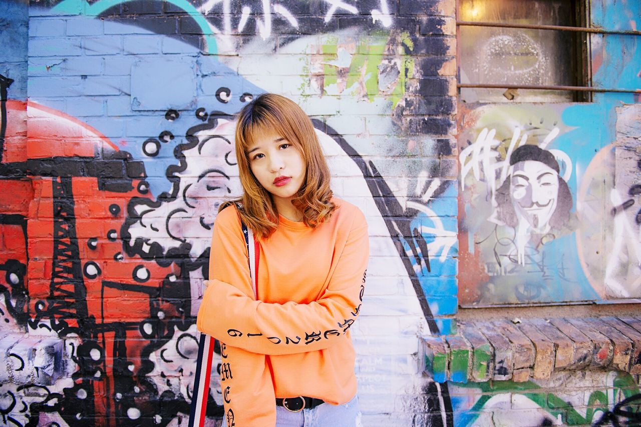 PORTRAIT OF YOUNG WOMAN STANDING BY GRAFFITI ON WALL