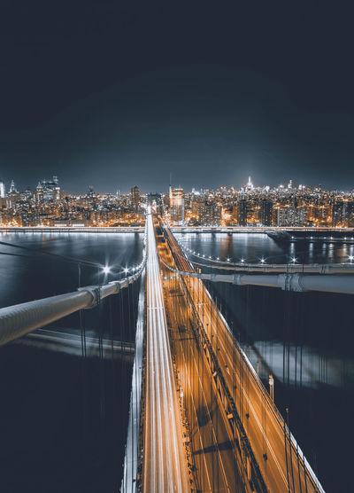 Illuminated bridge in city against sky at night