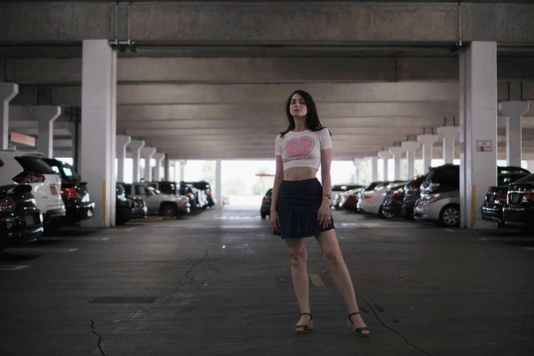 Full Length Portrait Of Woman Standing In Parking Lot