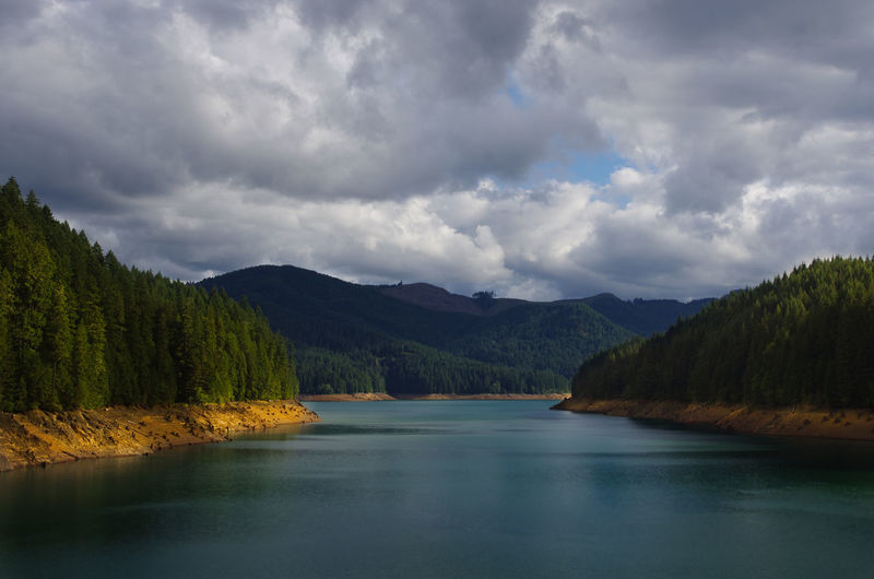 Scenic View Of Reservoir Against Mountains And Cloudy Sky