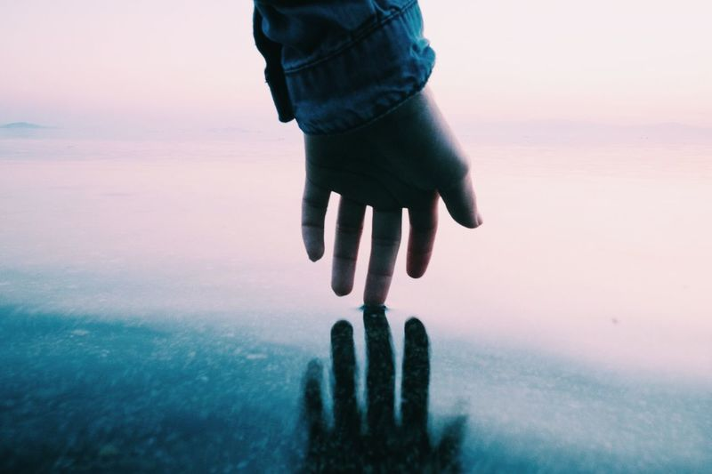 Cropped hand of woman touching sea shore