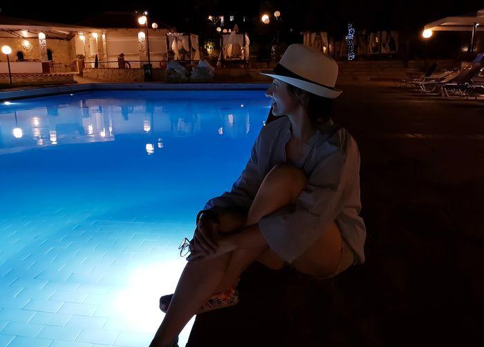 Woman sitting in swimming pool at night