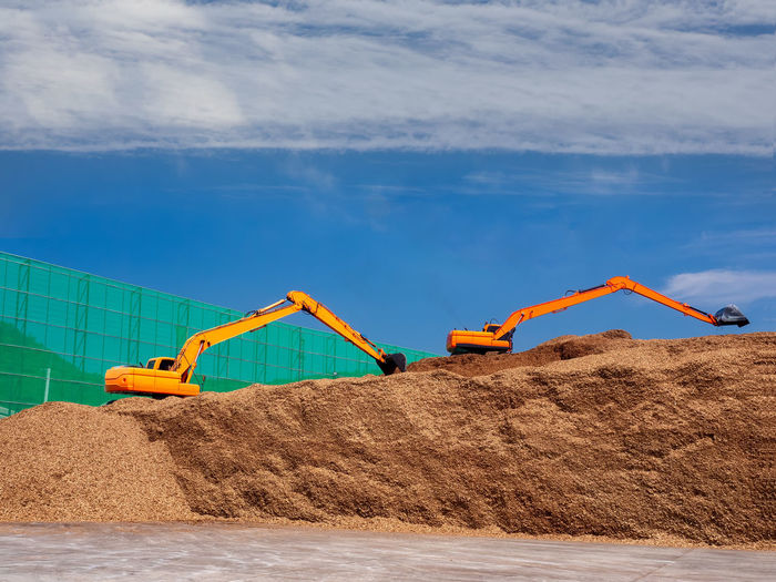Pile of wood chips to storage for export by backhoe
