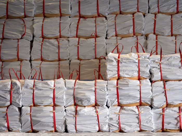 White jumbo bags of sugar stack inside warehouse Jumbo Rice Sling Stack Sugar Abundance Arrangement Backgrounds Bags Full Frame In A Row Industry Large Group Of Objects Market Order Pattern Red Repetition Side By Side Still Life Store Tapioca Textile Tied Up Warehouse