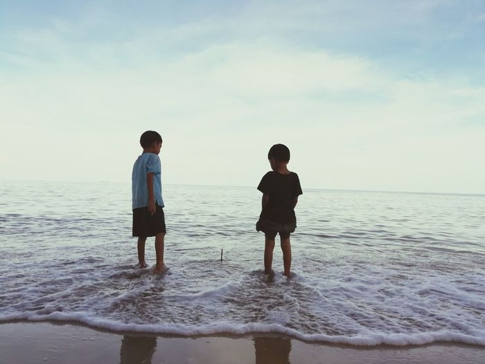 Siblings Standing In Sea Against Sky